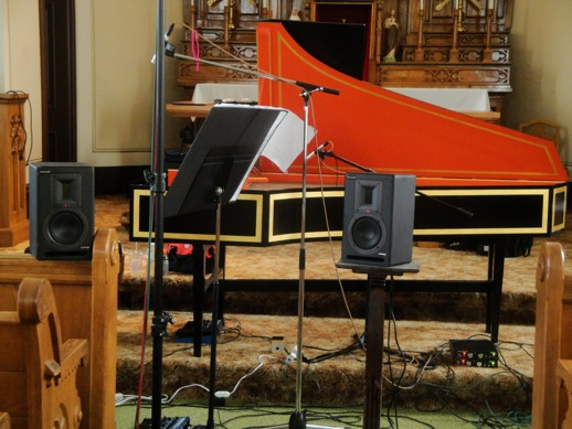 Loudspeakers, pedals, and preamps greet you with strange beady eyes, especially when placed in front of a harpsichord